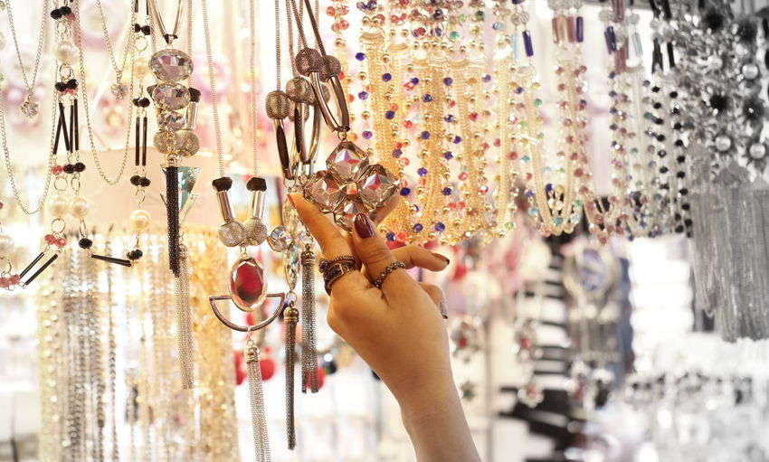 Close-up of woman buying necklace in market