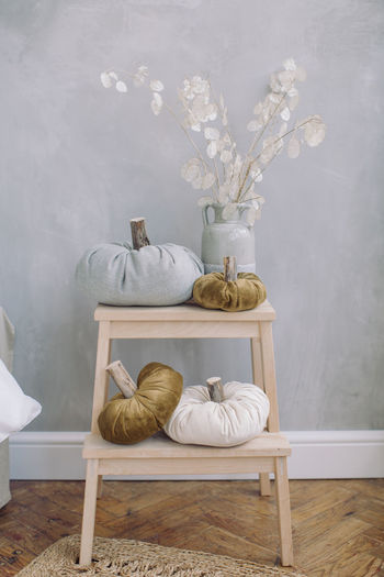 Flower vase and pumpkins on table against wall at home