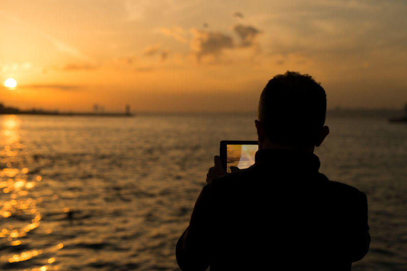 Rear view of silhouette boy photographing sea at sunset