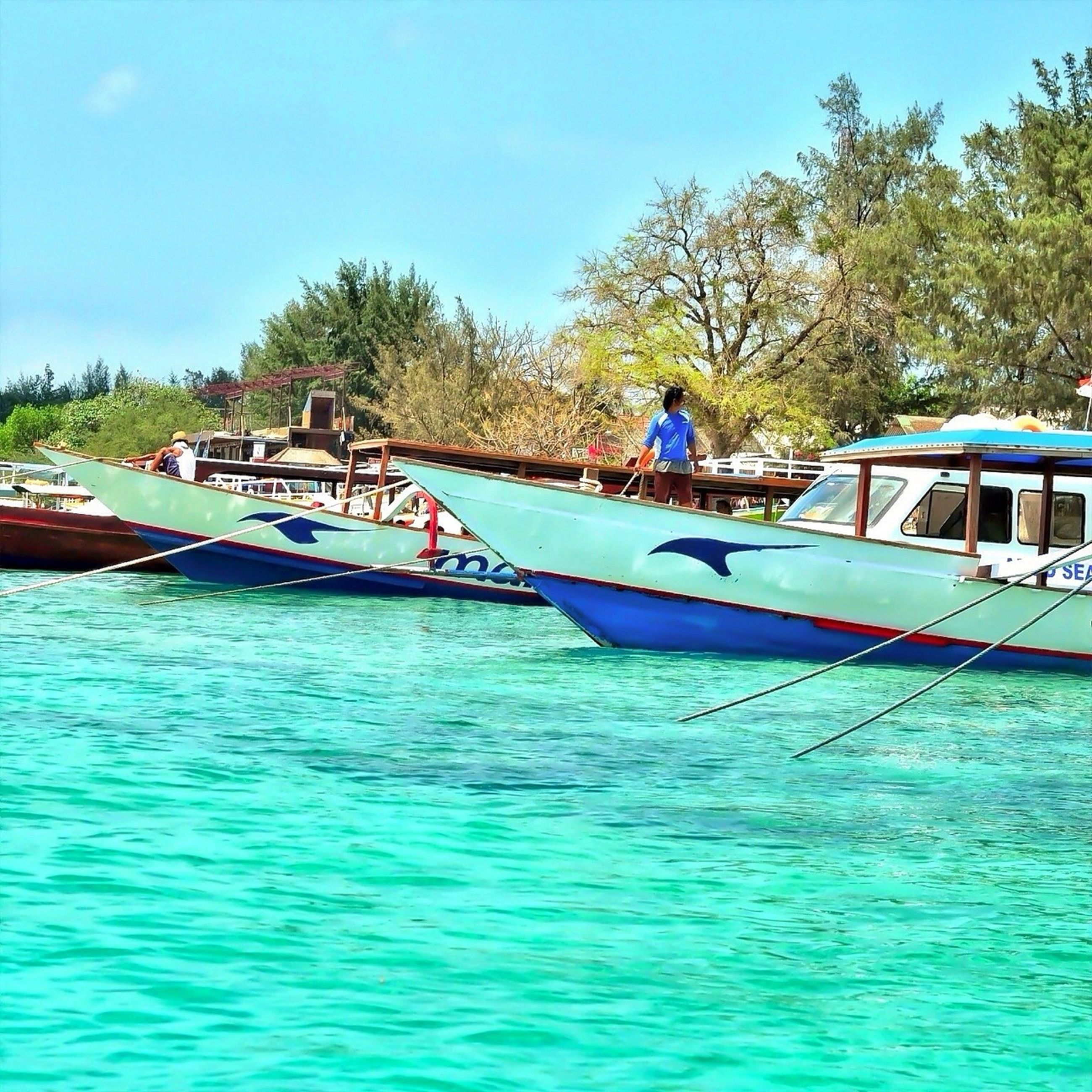 water, nautical vessel, transportation, mode of transport, tree, boat, waterfront, blue, leisure activity, lifestyles, men, travel, vacations, day, person, rippled, clear sky, nature