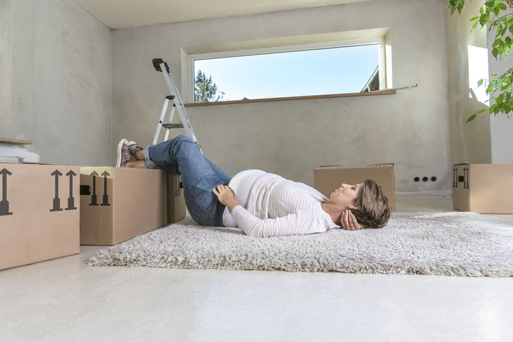Pregnant Woman Lying On Carpet At Home