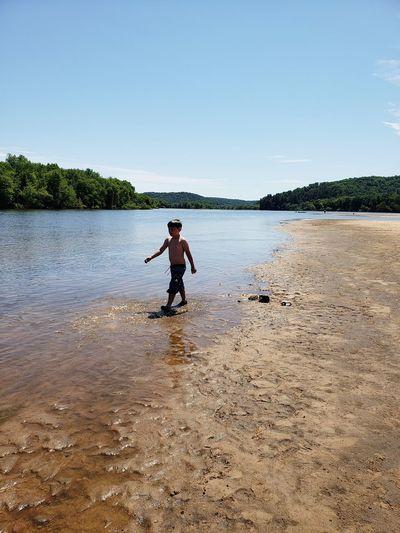 Boy walking at lakeshore against sky
