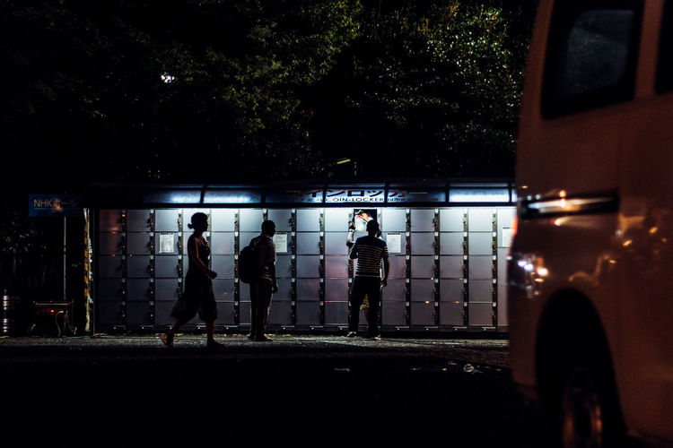 People By Illuminated Lockers At Night