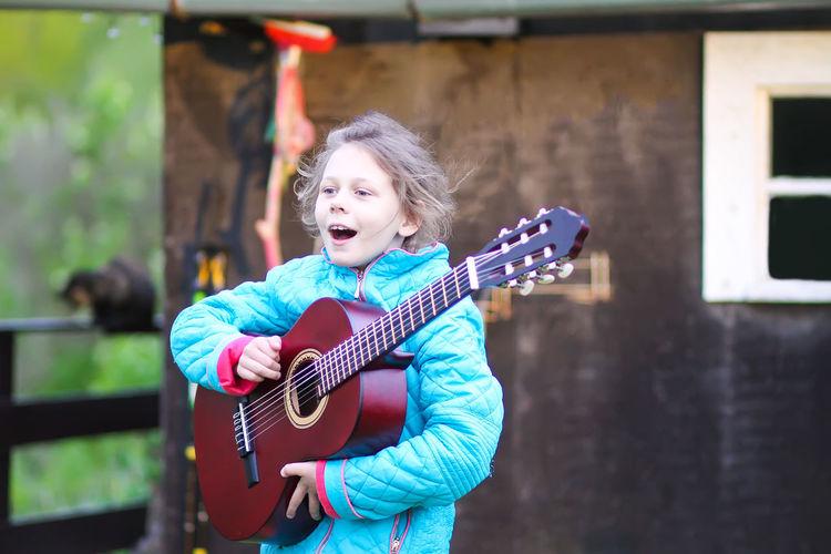 Cute girl playing guitar outdoors