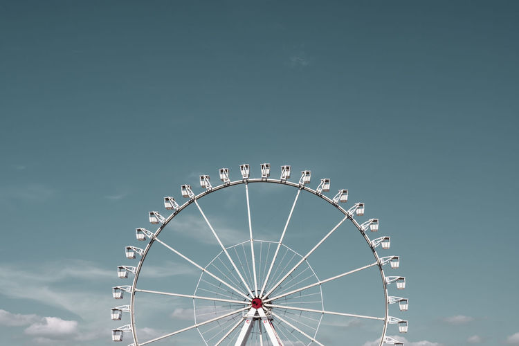 Low angle view of ferris wheel against sky on sunny day