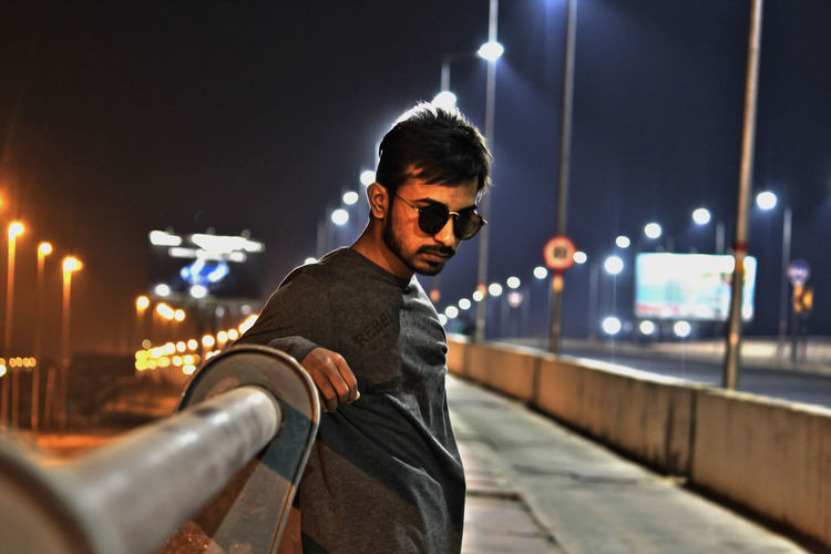 Portrait of young man wearing sunglasses while standing by railing at night