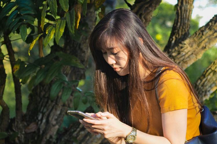 Teenage girl using mobile phone outdoors
