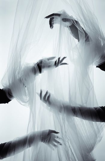 Cropped Hands Of Women Wrapped In Plastics Against White Background