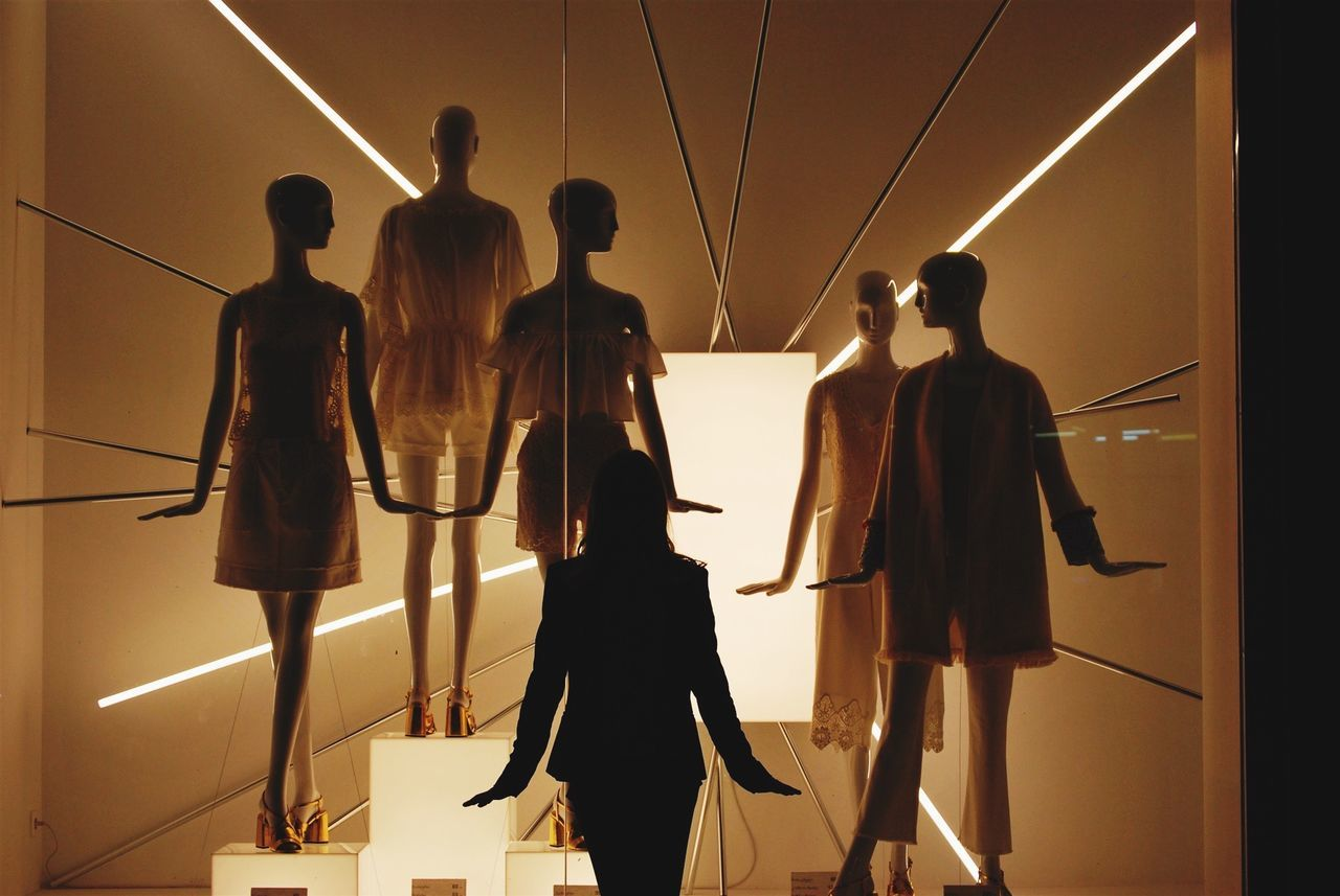 Rear view of woman standing against mannequins