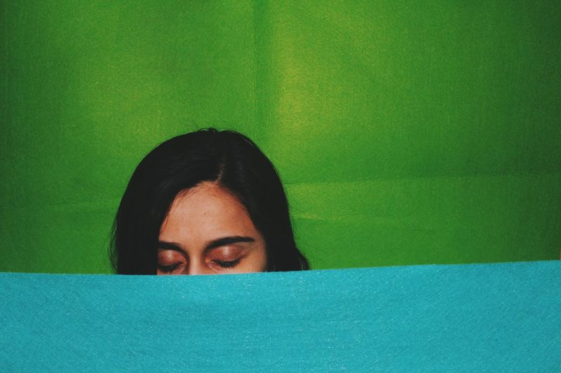 Close-up of woman with eyes closed amidst green and turquoise fabrics
