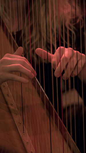 Midsection of woman playing harp