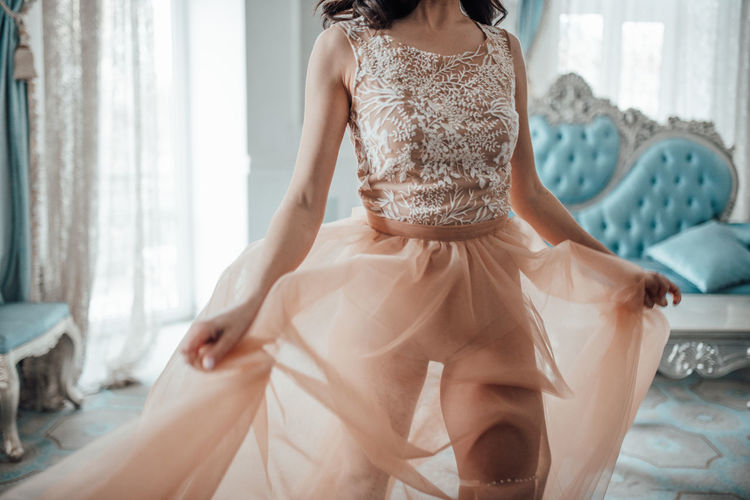 Midsection of woman wearing bridal dress standing at home