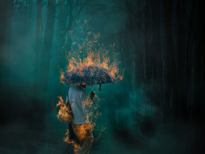 Digital composite image of woman standing with burning umbrella at night in forest