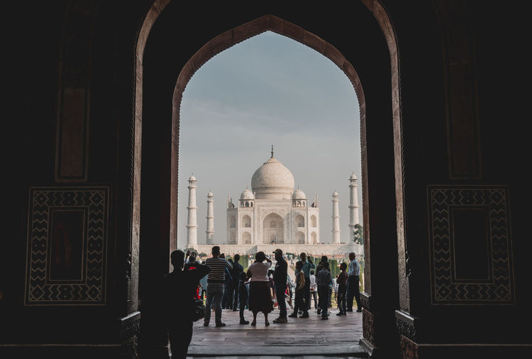 People seen through arch standing in front of taj mahal