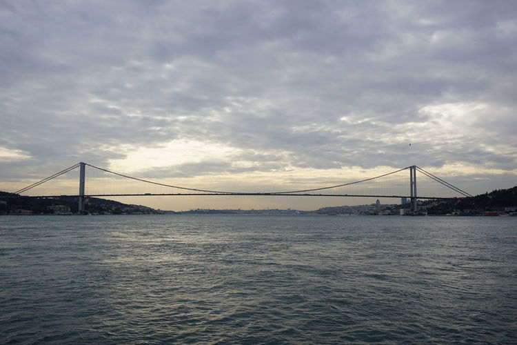 Low angle view of bosphorus bridge over sea against cloudy sky