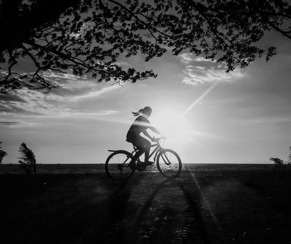 Side View Of Silhouette Woman Riding Bicycle By Sea Against Sky During Sunny Day