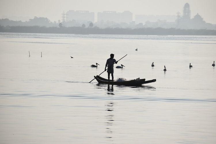 Silhouette man rowing boat in sea against sky