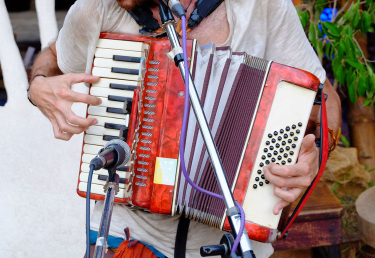 Midsection of man playing accordion outdoors