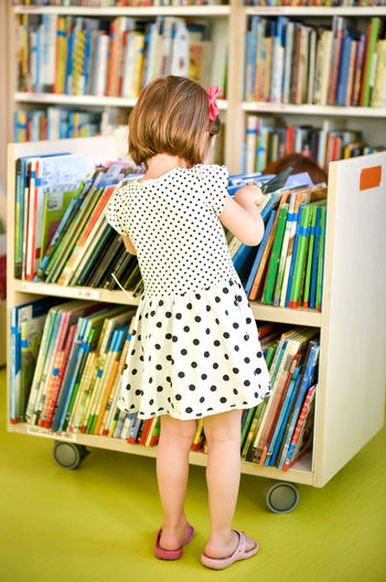 Rear view of girl selecting book while standing in library