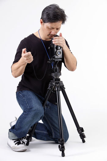 studio shot of photographer capturing images Photographer Camera Old Hobbies Human Face Human Hand People Photography Phtographing Antique Medium Format Camera Holding Capturing Capturing An Image Tripod Cable Cable Release White Background Studio Shot Man Males  One Person Indoors  Full Length Cut Out Front View Mid Adult Casual Clothing Technology Photography Themes Camera - Photographic Equipment Activity