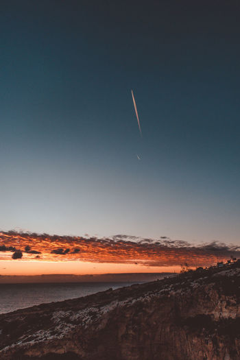 Scenic view of vapor trails in sky during sunset
