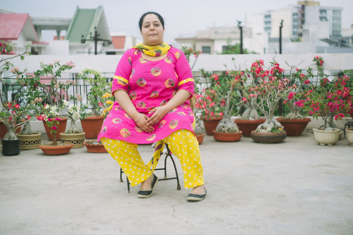 FULL LENGTH PORTRAIT OF SMILING WOMAN SITTING ON CHAIR AT PARK