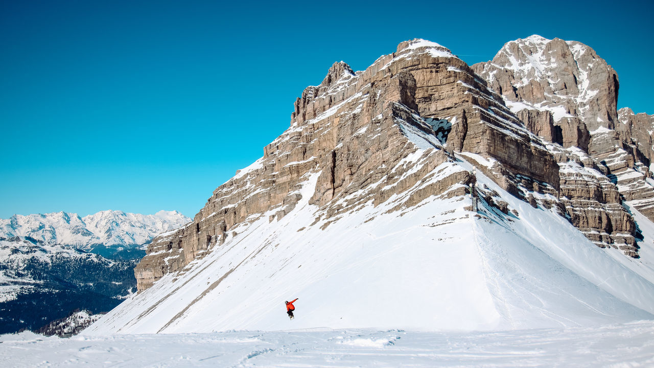 Distant View Of Person Practicing Snowboard Stunt Against Dolomites During Winter