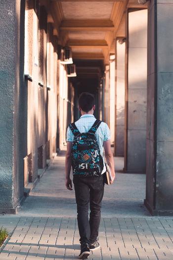 Young man walking in corridor at university