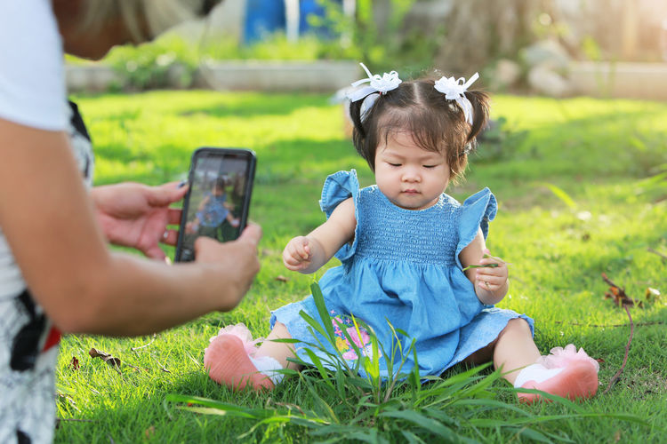 Woman photographing daughter at park