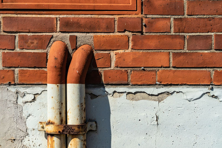 Architecture Brick Brick Wall Brown Building Exterior Built Structure Close-up Connection Day Metal No People Old Orange Color Outdoors Pattern Pipe - Tube Red Textured  Wall Wall - Building Feature