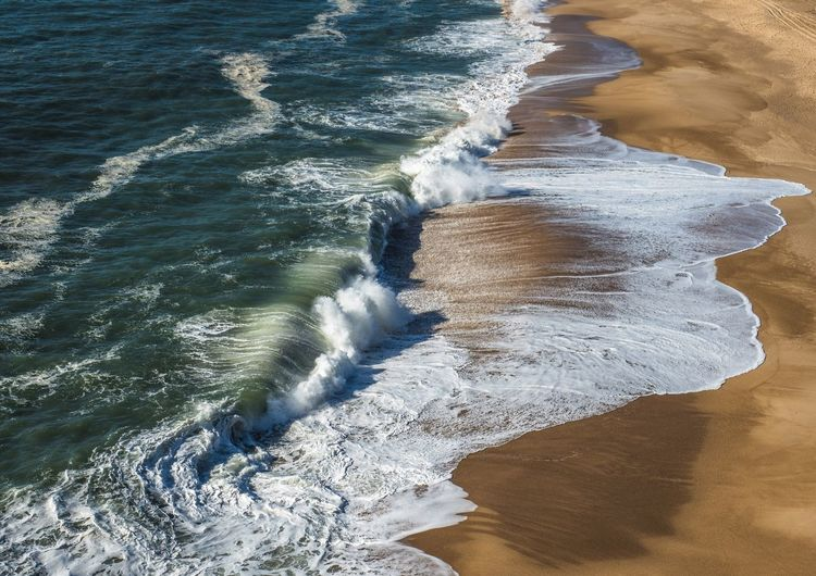 Waves on the beach of Nazaré Wave Sea Beach Sand Surf Shore Nature Beauty In Nature Water Scenics No People Motion Day Outdoors Power In Nature Force Nazaré  Portugal Holiday Vacations Travel Destinations Lost In The Landscape