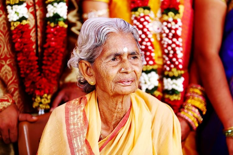 Senior Woman In Sari Looking Away While Sitting On Chair