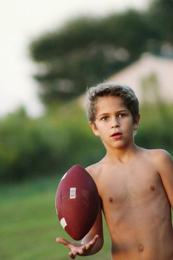 Portrait of shirtless boy holding ball