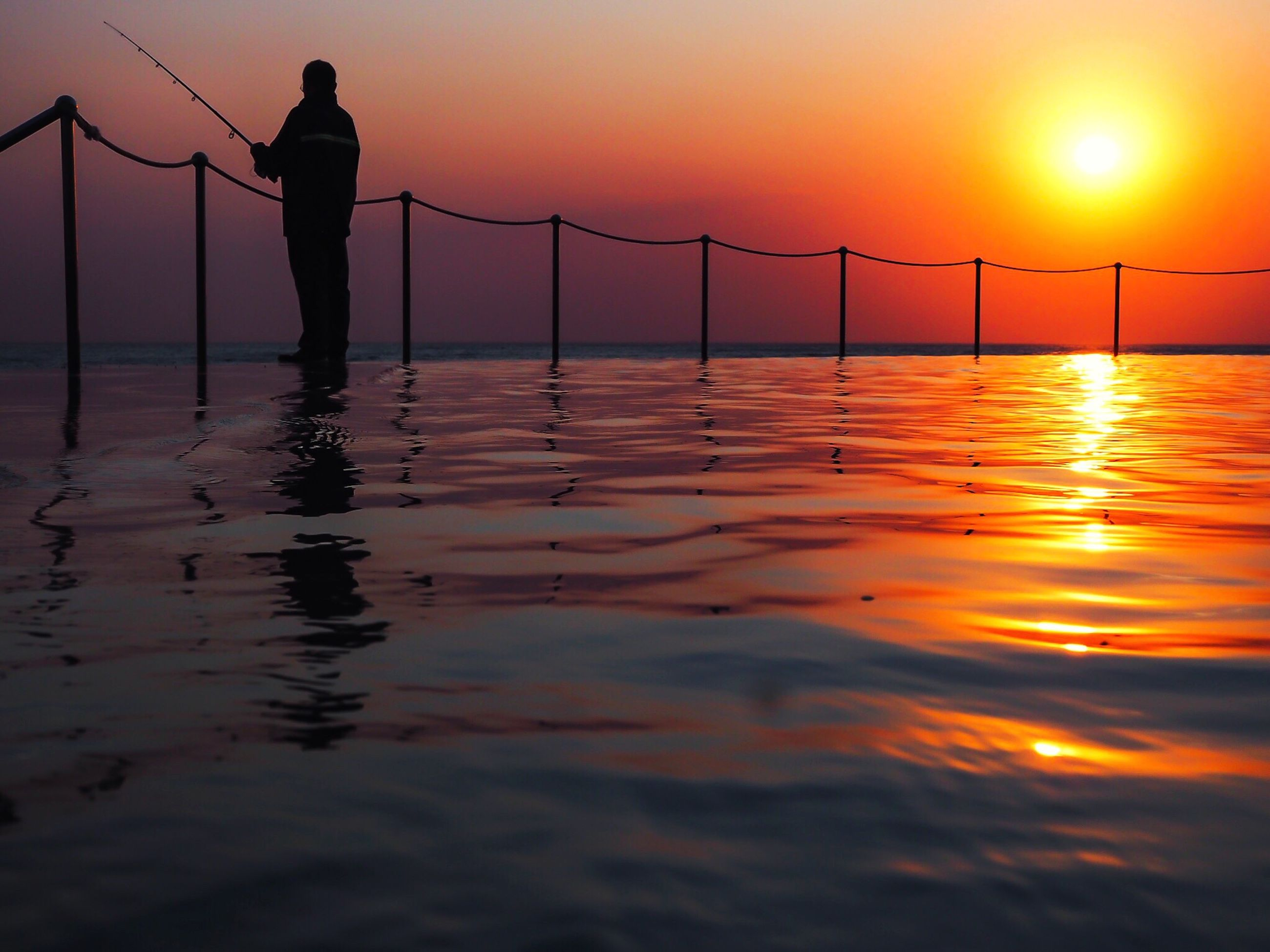 water, sunset, real people, silhouette, sea, waterfront, nature, reflection, beauty in nature, men, scenics, sky, one person, standing, outdoors, fishing, lifestyles, fisherman, full length, horizon over water, occupation, working, fishing pole, day