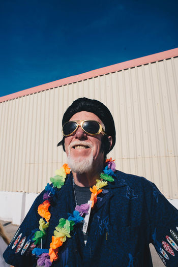 Portrait of man wearing sunglasses standing against sky