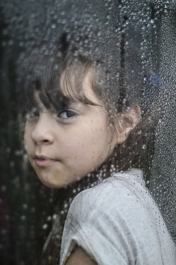 Close-Up Portrait Of Girl Looking Through Window