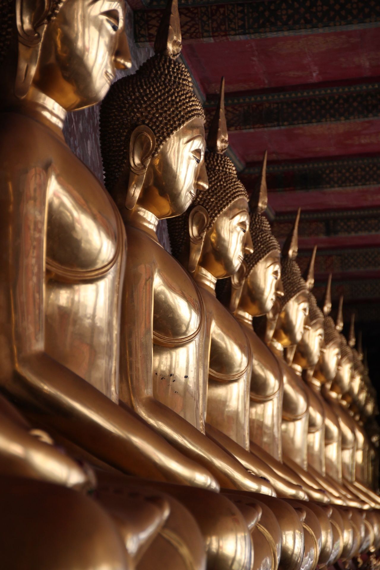 Rows of golden buddha statues at temple wat suthat