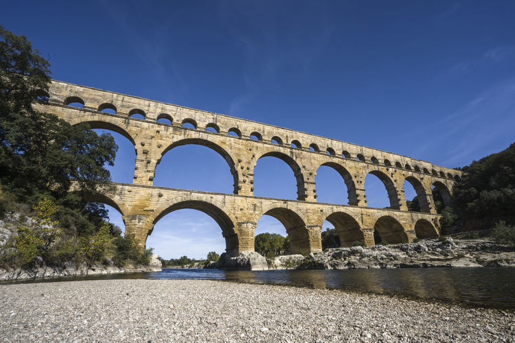Low angle view of arch bridge against blue sky