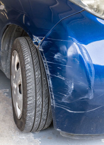 Blue scratched car with damaged paint in crash accident or parking lot Automobile Crash Damage Paint Rust Accident Auto Blue Bodywork Broken Bumper Car Collision Damaged Dent Dented Dirty Insurance Metal Repair Safety Scratch Scratched Scratches Tire