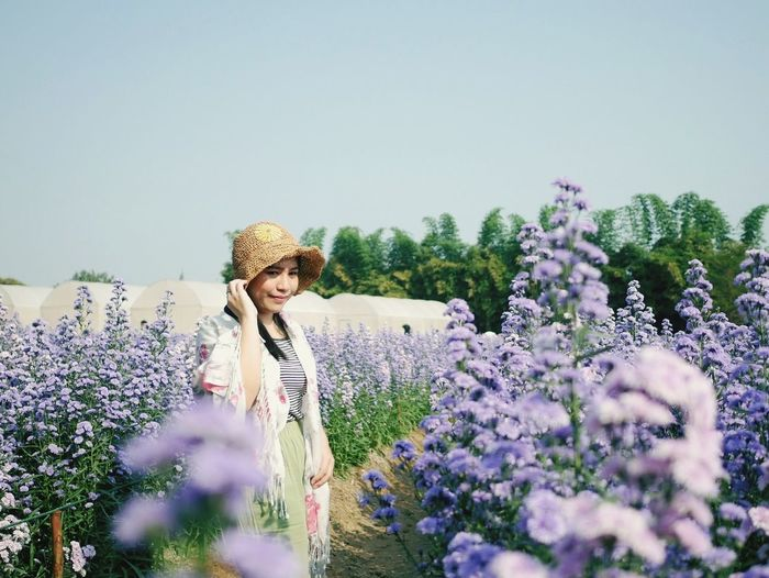 Young woman standing on lavender amidst flowering plants against clear sky