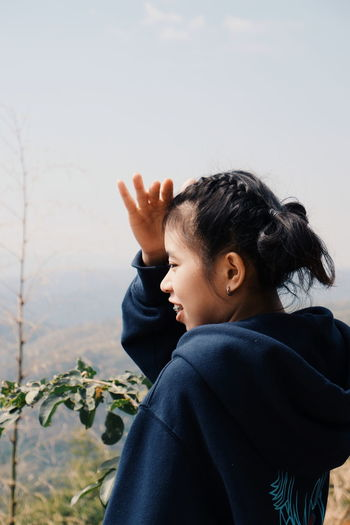 Side view of woman shielding eyes against sky