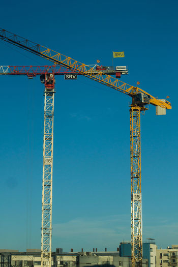 Machinery Sky Crane - Construction Machinery Construction Site Blue Construction Industry Industry Clear Sky Development Architecture Low Angle View Metal Day Built Structure No People Tall - High Construction Equipment Outdoors Sunlight Industrial Equipment