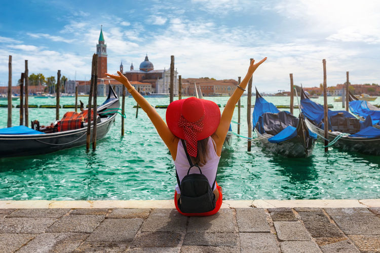 Rear View Of Woman With Arms Raised Sitting At Grand Canal