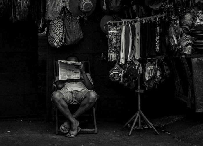 Man reading newspaper in shop at market