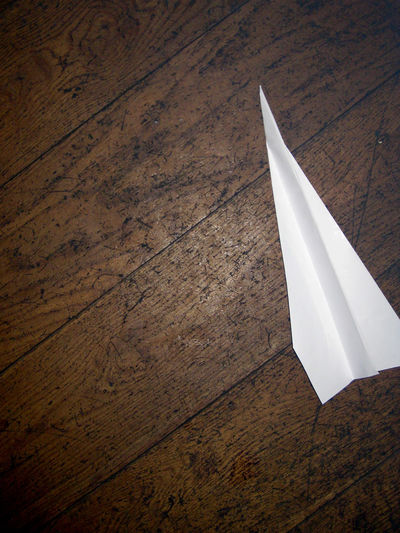 Paper Airplane On Hardwood Floor