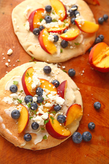 Fresh peaches and blueberries on pizza with feta