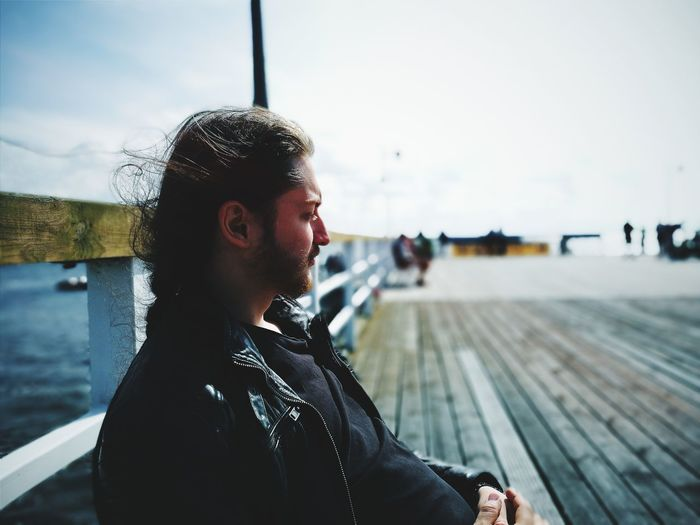Young man looking away while sitting by railing against sky