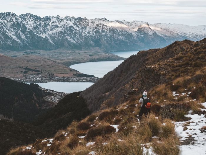 Rear View Woman Standing On Snowcapped Mountains During Winter