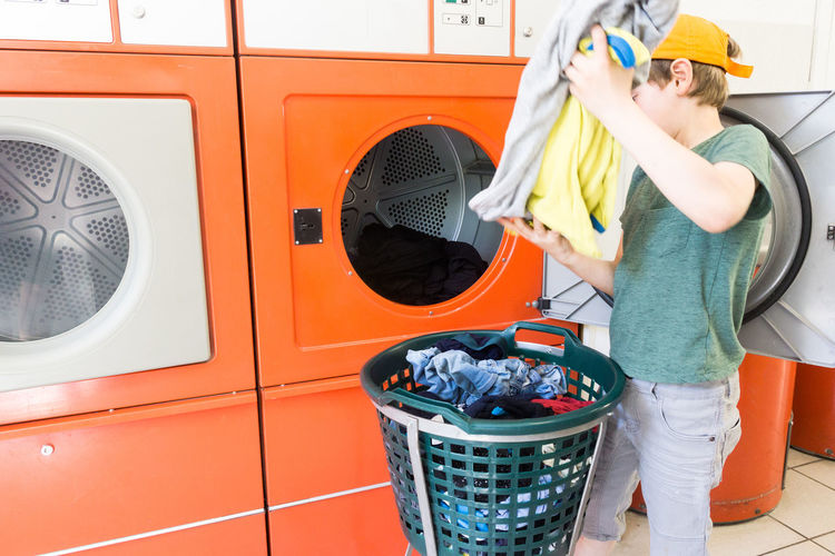 Boy putting clothes in washing machine at home