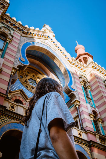 Low angle view of woman standing by church in city